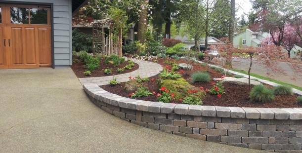 Landscaped yard with curved paver sidewalk retaining for Curved garden wall designs